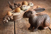 Brown easter eggs with antique bunny on wood — Stock Photo