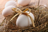 White egg with straw bow in nest on wood — Stock Photo