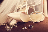 Wedding shoes with veil and rings on velvet chair — Stock Photo