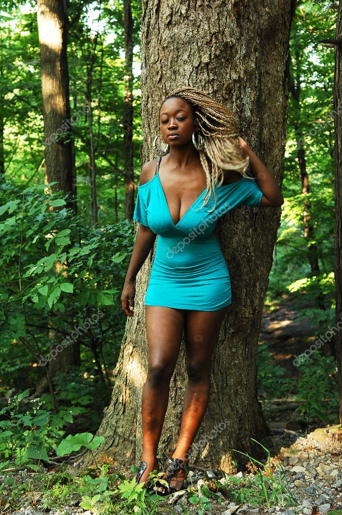 An Jamaican woman in a short turquoise dress leaning on a big treein the forest, shooing her nice figure and long hair.  Stock Photo #4591176