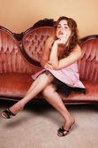 Pretty girl sitting on pink sofa. — Stock Photo