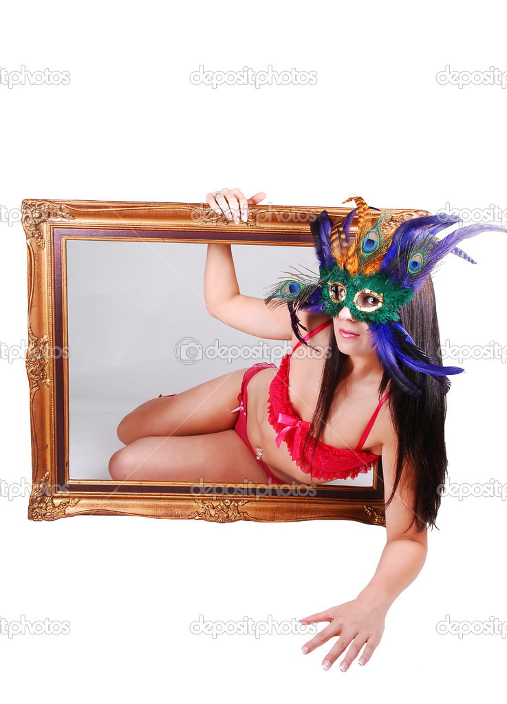 Lovely woman in red lingerie with a mask over her face looking througha picture frame with gray background inside and white background outside. — Stock Photo #4714600