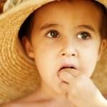 Little boy in straw hat eats — Stock Photo #3998556