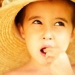 Naughty little boy in straw hat eats — Stock Photo #3998557