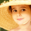 Naughty little boy in straw hat shows raspberry — Stock Photo #3998560