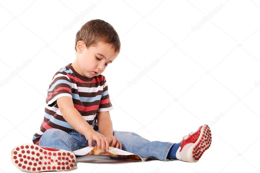 Boy sitting on the floor reading magazine isolated on white — Stock Photo #4096739