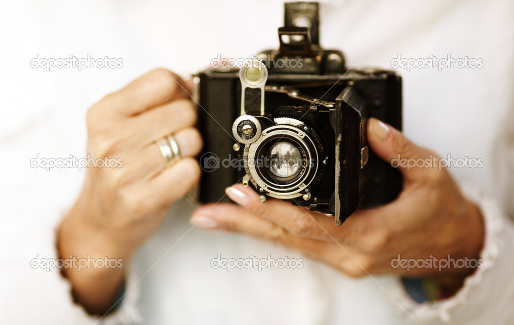 Woman hands with old film camera ,selective focus point on lens ,natural light — Stock Photo #4112176