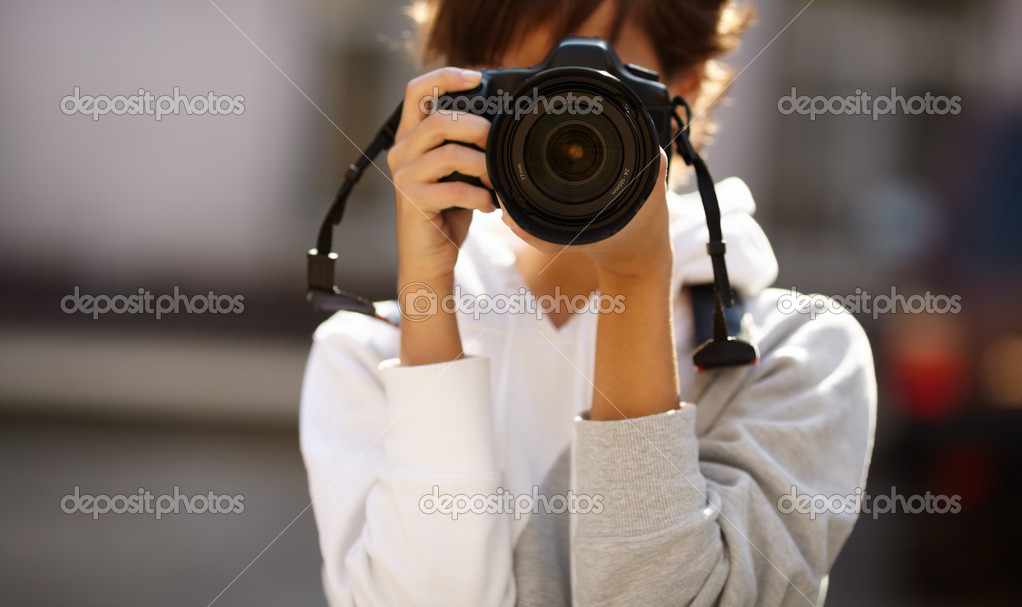 Female photographer with professional SLR camera, natural light, selective focus on nearest part of lens with blend  Stock Photo #4219156