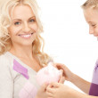 Mother and little girl with piggy bank — Stock Photo