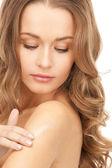 Beautiful woman with moisturizing creme — Stock Photo