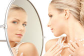 Beautiful woman with pearl beads and mirror — Stock Photo