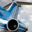Rear detail with engine, tail-plane and windows against a cloudy sky — Stock Photo