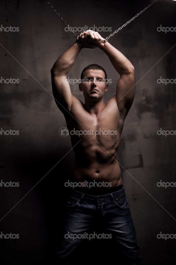 Young male model well build with chains over his arms — Stock Photo #5290185