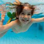 flicka leenden, simma under vatten i poolen — Stockfoto