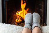Children's feet are heated in the fireplace — Stock Photo