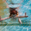Stock Photo: The girl smiles, swimming under water in the pool