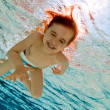 The girl smiles, swimming under water in the pool - Stock Photo