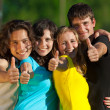 Young group of happy friends showing thumbs up sign — Stock Photo