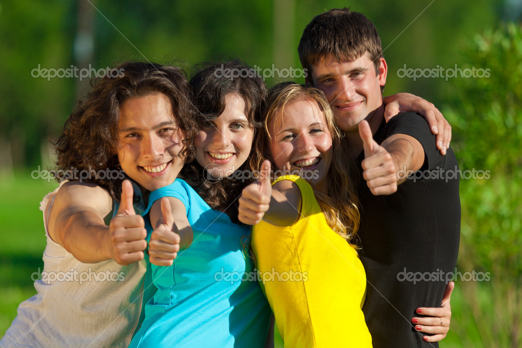 Young group of happy friends showing thumbs up sign together outdoor in the park — Stock Photo #4081923