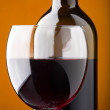 A bottle of red wine and a wine glass closeup — Stock Photo
