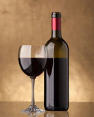 A bottle of red wine and filled a wine glass — Stockfoto