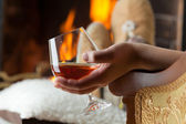 Resting at the burning fireplace fire with a glass of cognac — Stock Photo