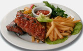 Pork ribs under a red sauce with fries — Stock Photo