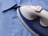 Ironing blue shirt — Stock Photo