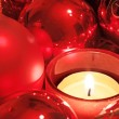 Red Christmas balls and tea light — Stock Photo