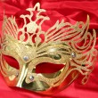 Gold mask on red background — Stock Photo