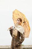 Frau mit regenschirm orange — Stockfoto