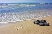 Inscription SOS in the sand with slippers — Stock Photo