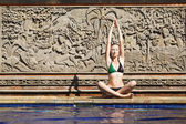 Woman playing yoga beside the swimming pool — Stock Photo