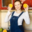 Stock Photo: Pregnant womat kitchen with orange