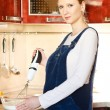 Stock Photo: Pregnant woman in kitchen making a food