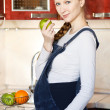 Stock Photo: Beautiful pregnant womat kitchen with apple