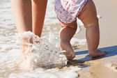Pretty wonam walking in water with her baby — Stock Photo