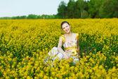 Woman on yellow field — Stock Photo