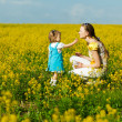 Mother with baby on field — Stockfoto