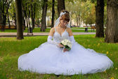 Bride with bouquet sits on the grass in the park — Stockfoto