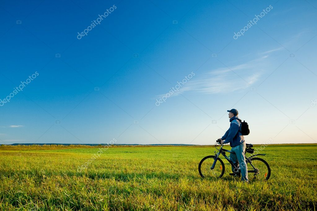 Man on bike in  green field — Stock Photo #4141231