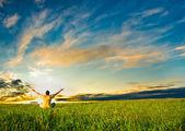 Człowiek siedzi w polu pod zachód słońca — Zdjęcie stockowe