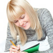 Woman writing and smiling — Stockfoto