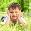 Happy little boy laying on the grass — Stock Photo