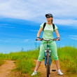 Woman with bike on green field — Stock Photo