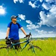 Man with bike on green field — Stockfoto