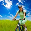 Woman with bike on green field — Stok fotoğraf