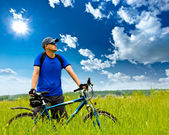 Man with bike on green field — Stock Photo
