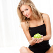 Beautiful woman sitting on bed and holding apple — Stock Photo