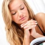 Блондинка женщина лежа на кровати и читать книги — Стоковое фото